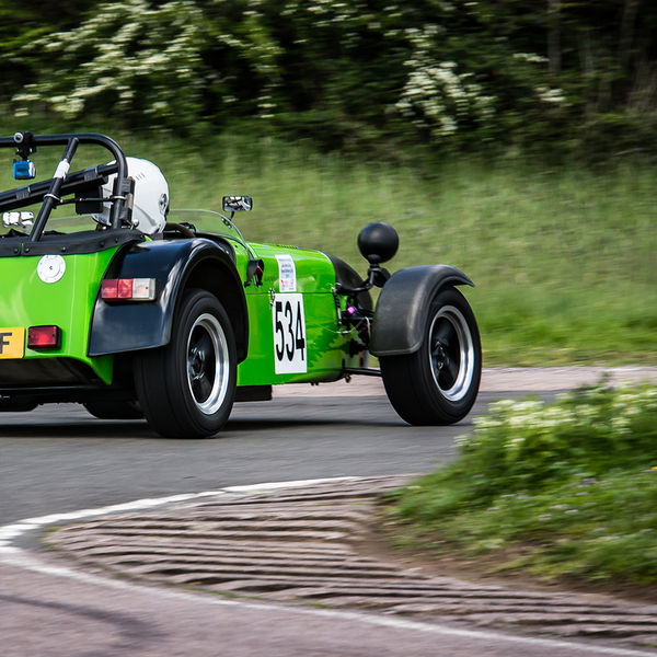 Bright green Caterham 7 at speed round flag pole corner at shenstone sprint course