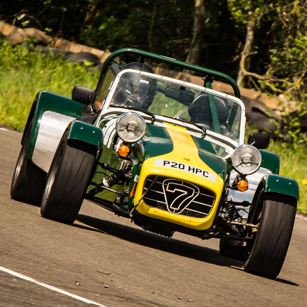 green and yellow caterham 7 at speed through curborough sprint course mole hill corner