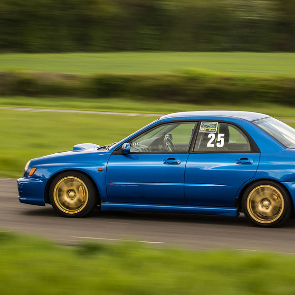 blue subaru impreza speeding along the curborough sprint straight