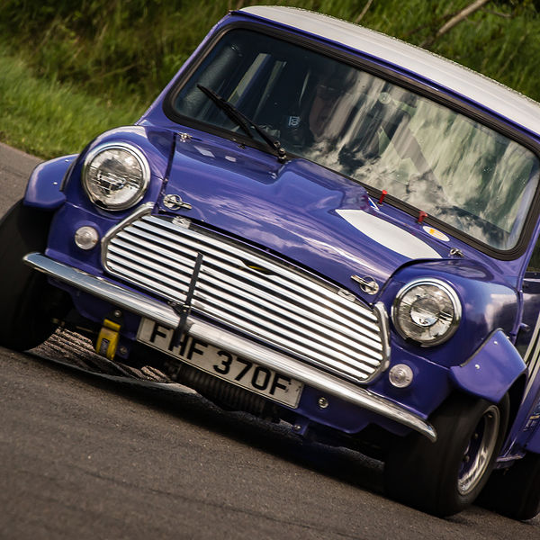 purple classic mini cooper cornering at speed