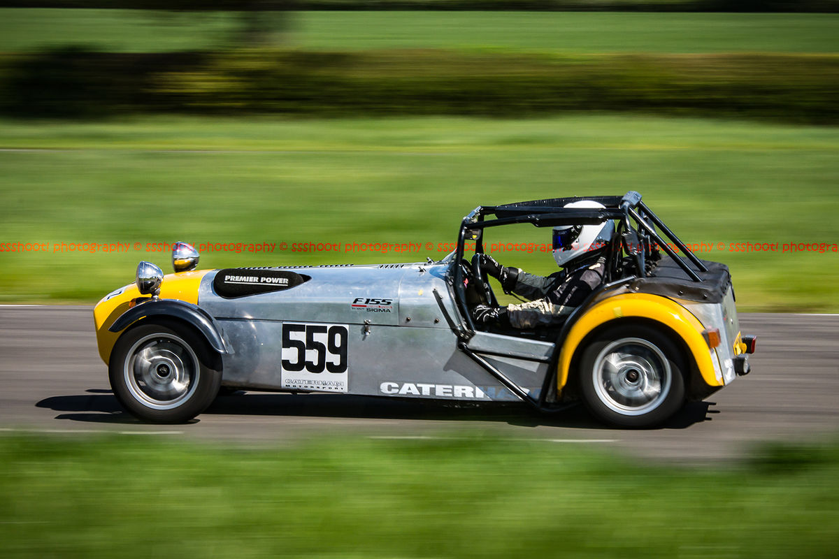 Yellow and silver Caterham 7 at speed along the Curborough sprint course shenstone straight