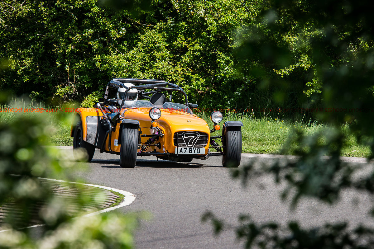 orange caterham 7 rounding the fradley hairpin corner at curborough sprint track