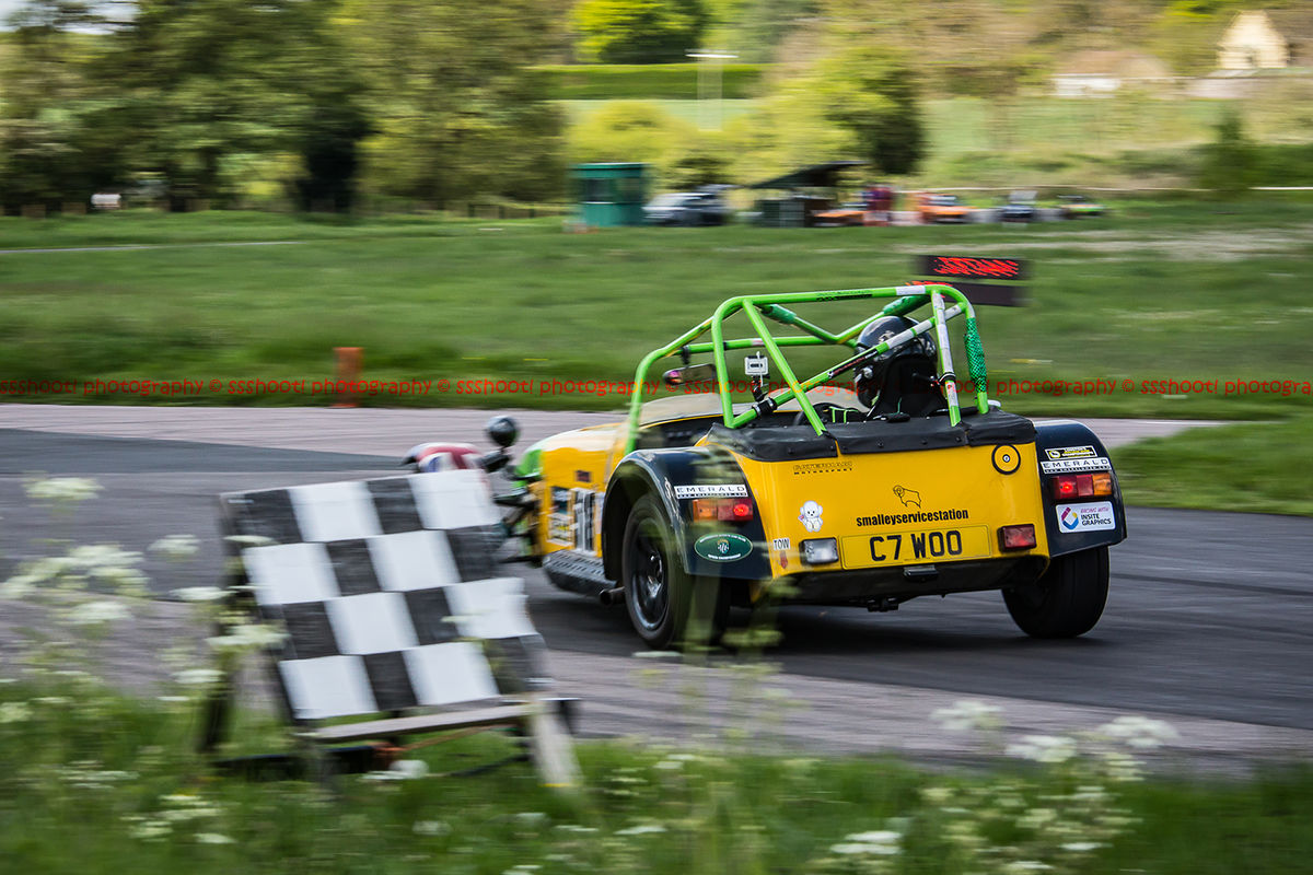 Yellow Caterham 7 at speed past the chequered flag at shenstone sprint course