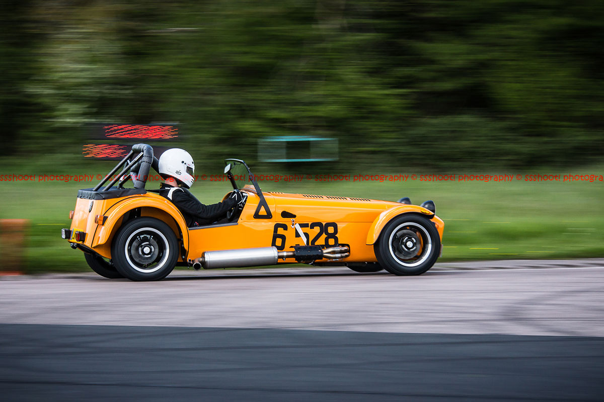 Orange Caterham 7 at speed through flag pole corner at shenstone sprint course