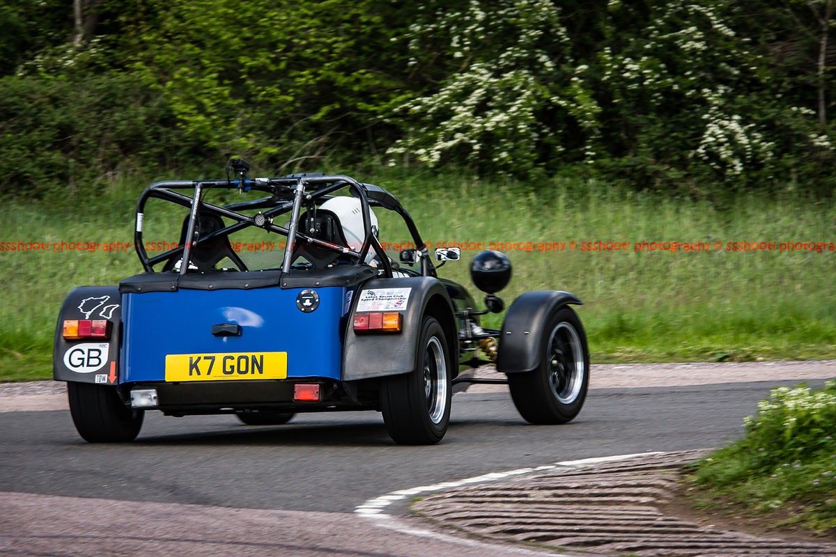Blue Caterham 7 at speed round flag pole corner at shenstone sprint course