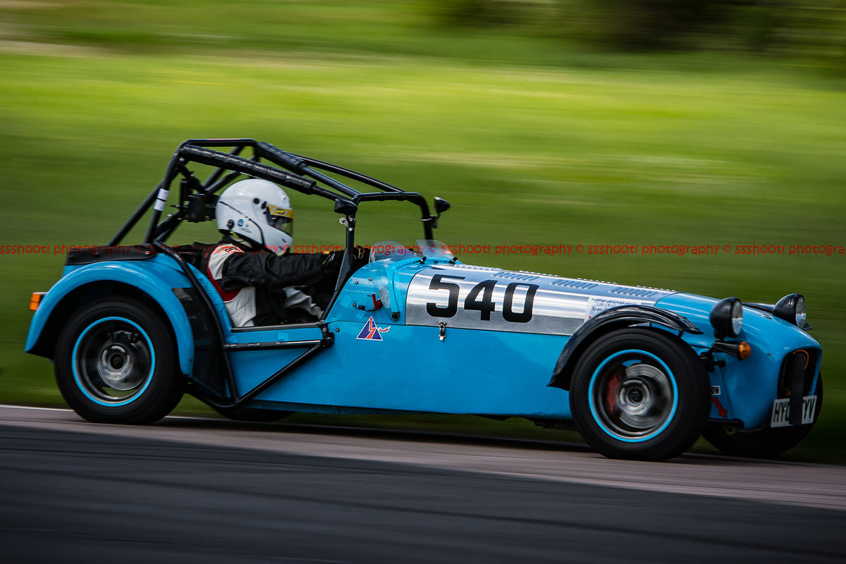 Blue caterham 7 at speed approaching flag pole corner at curborough sprint course