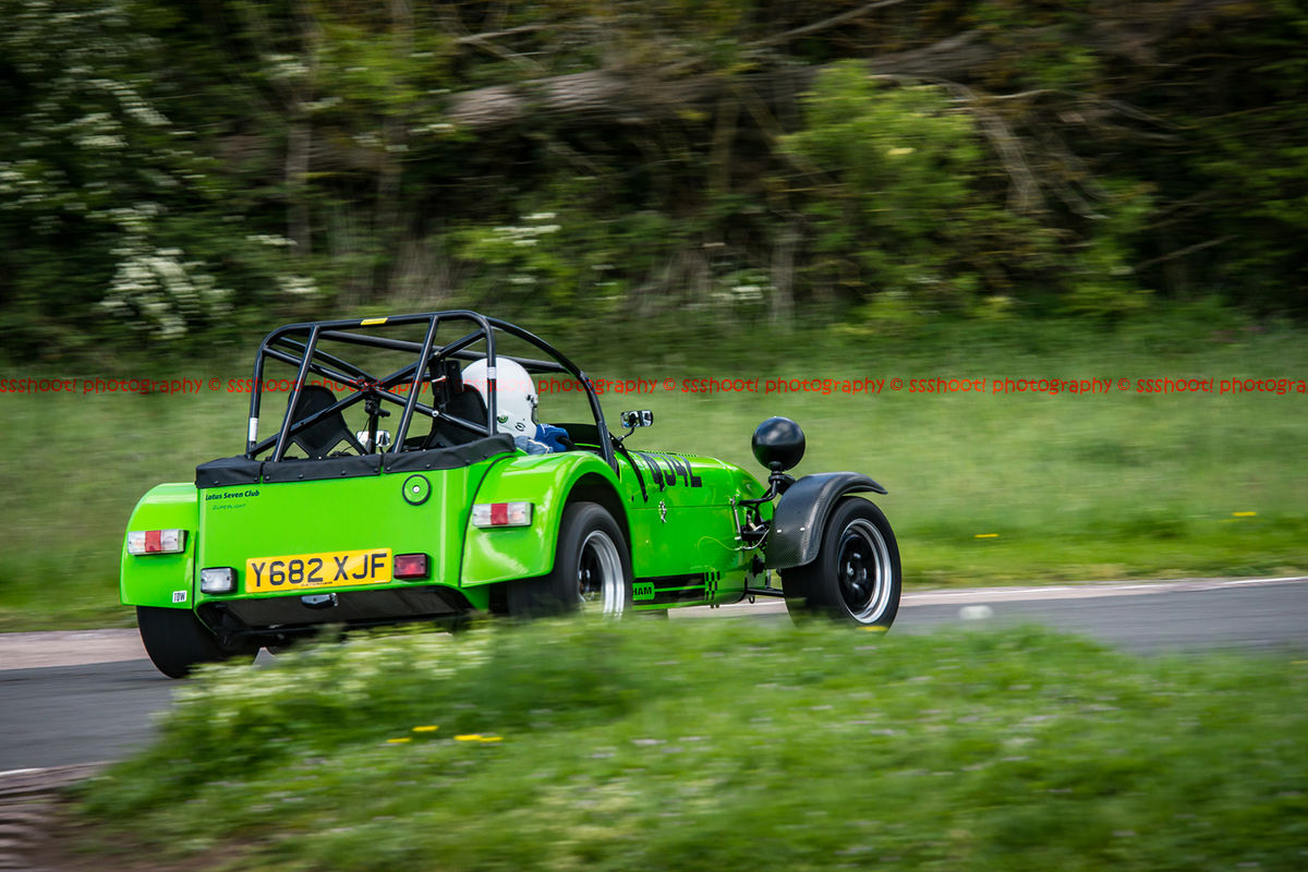 Bright green caterham 7 exiting flagpole corner at curborough sprint course