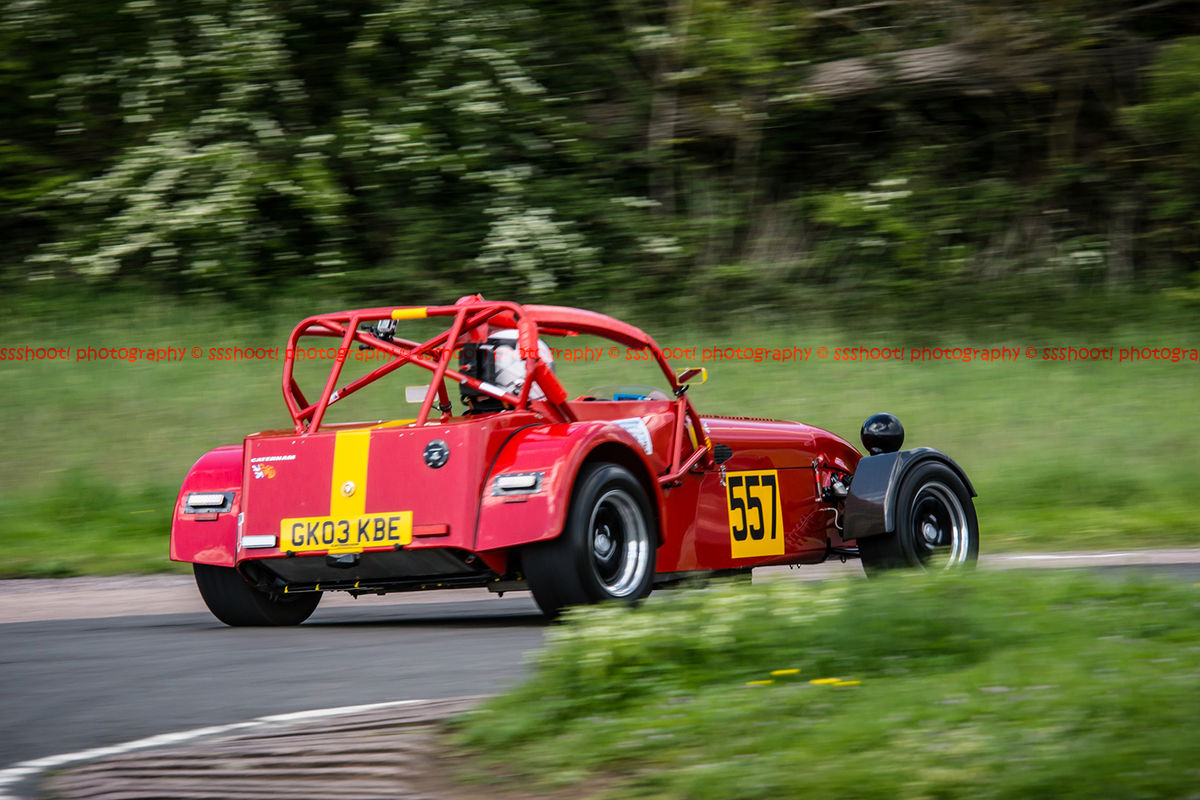 Red caterham 7 exiting flagpole corner at curborough sprint course