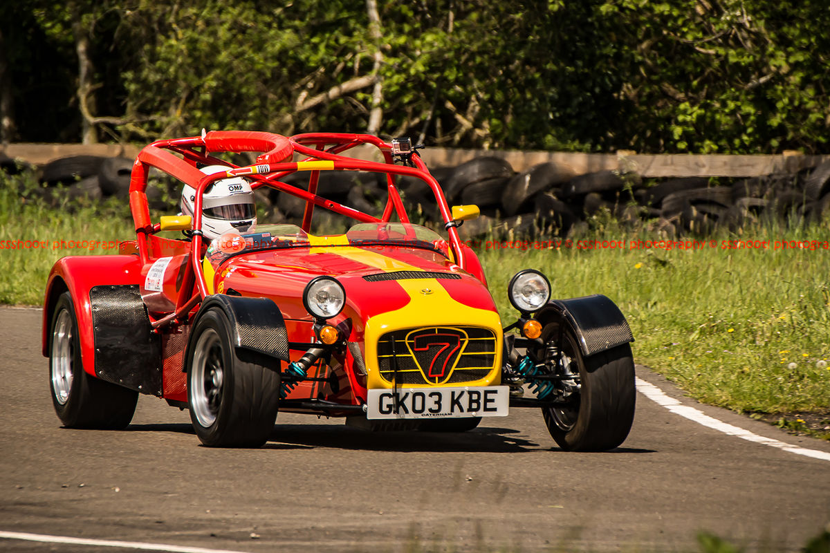 red and yellow caterham 7 at speed through curborough sprint course mole hill corner