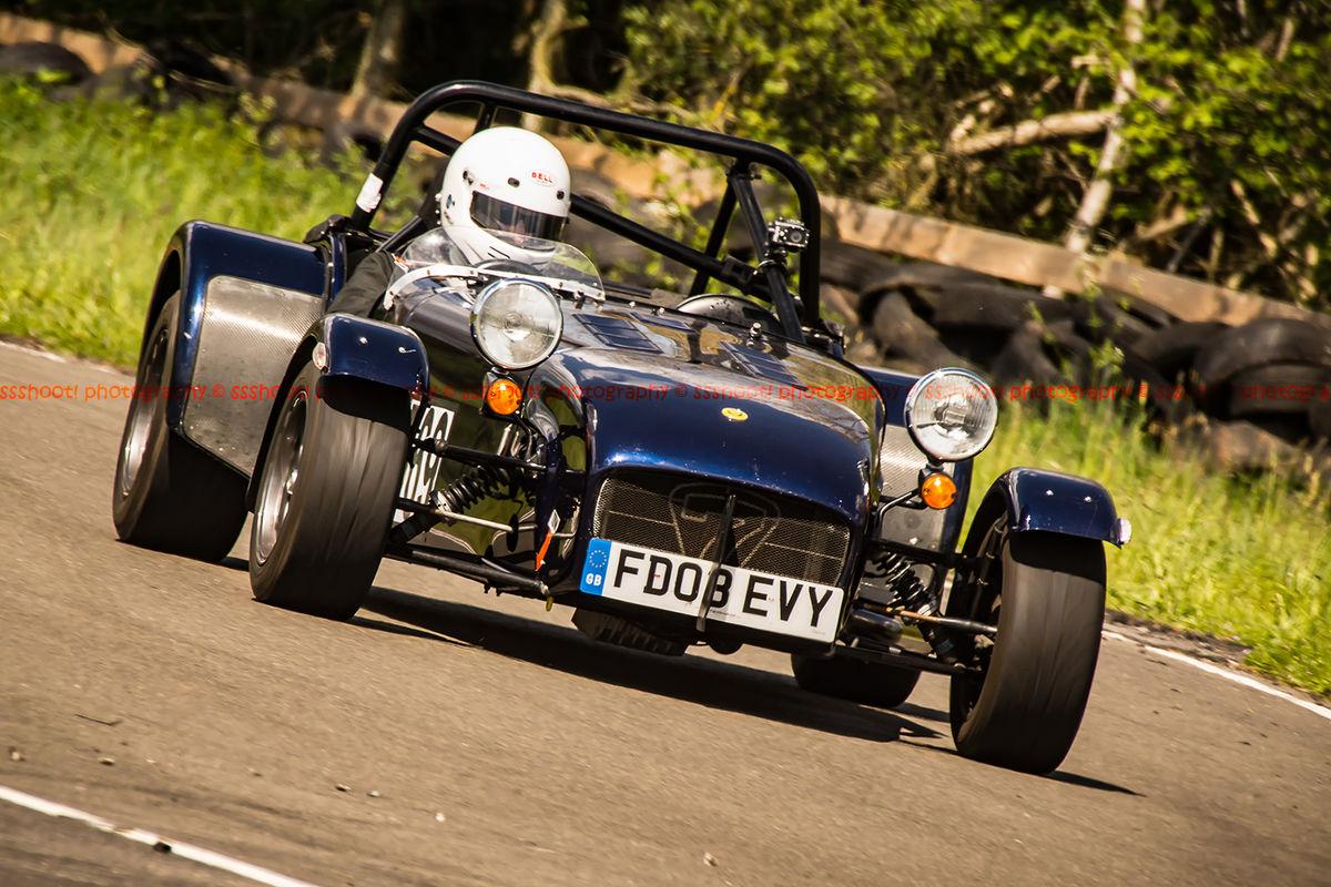 dark blue caterham 7 at speed through curborough sprint course mole hill corner