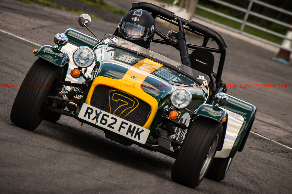 yellow and green caterham 7 rounding the fradley hairpin corner at curborough sprint track