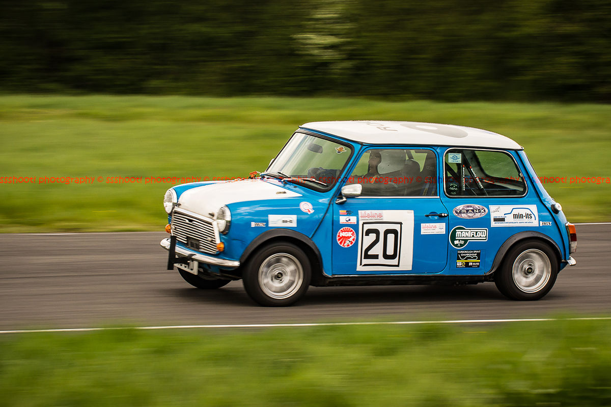 classic blue mini cooper s at speed along shenstone straight