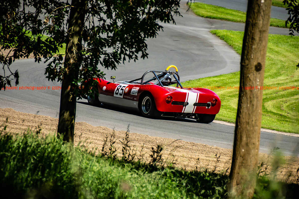 red classic sixties race car at speed during the porsche at prescott hill climb event
