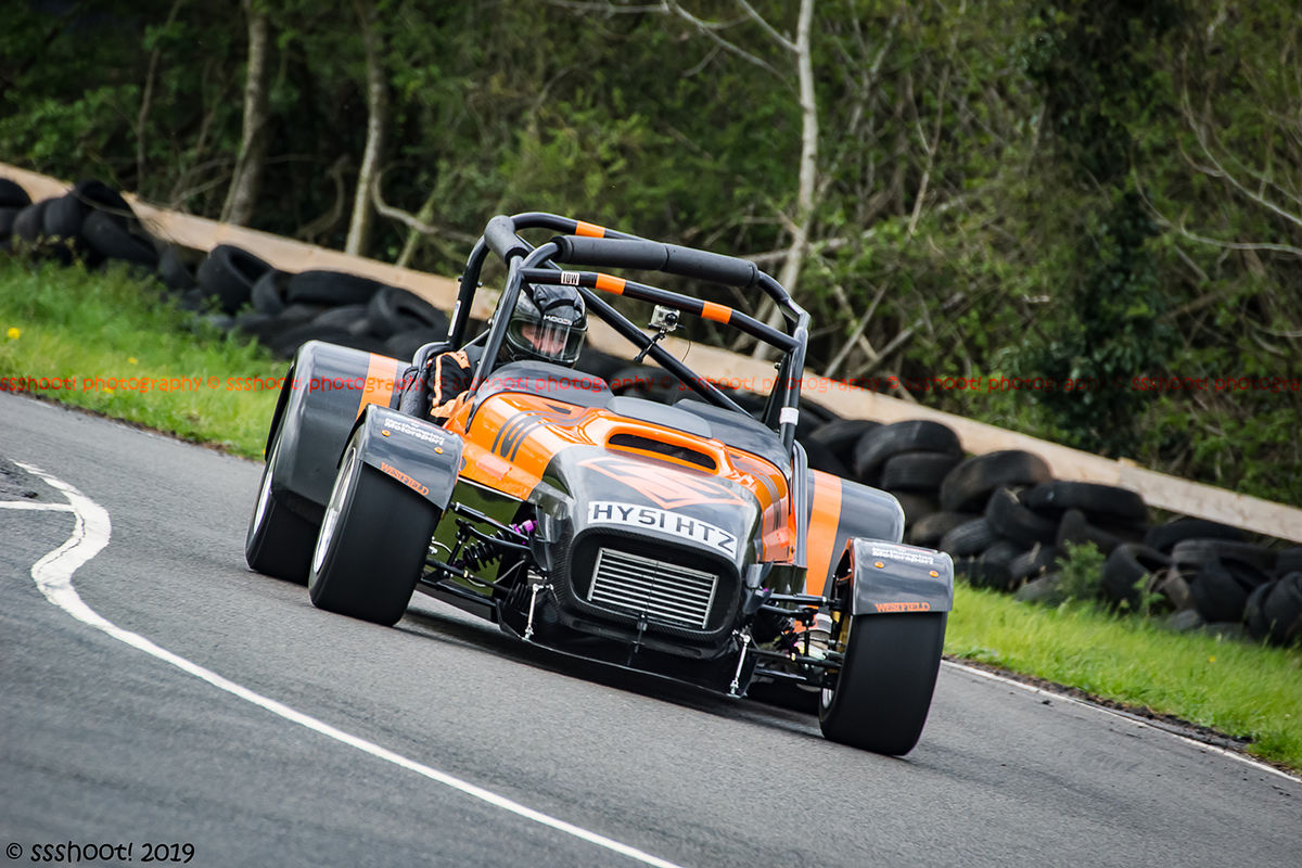 orange and black lotus 7 caterham westfield at speed through molehill corner at curborough sprint track
