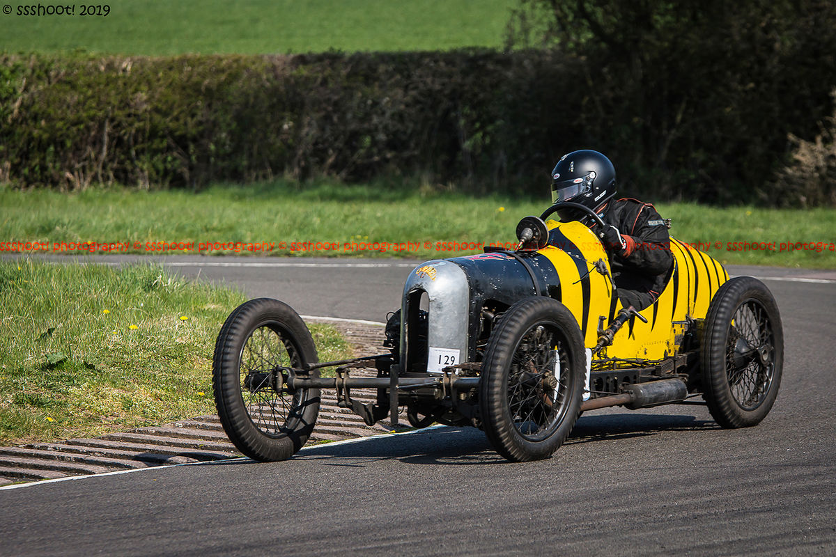 black and yellow striped vintage racing car at speed on curborough sprint course