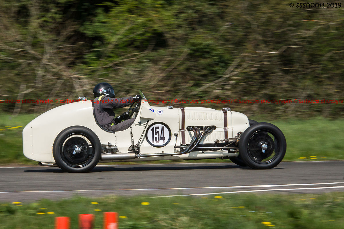 White vinage racing car taking on curborough sprint course at speed