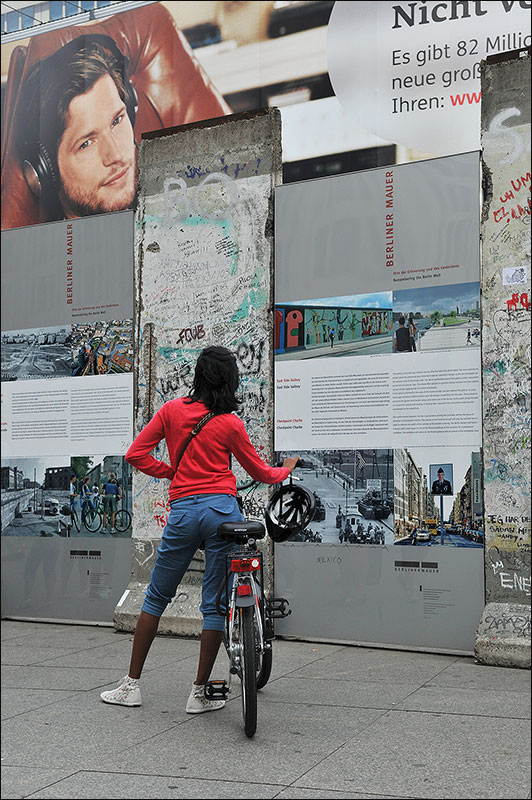 Girl on her bicycle at the wall.
