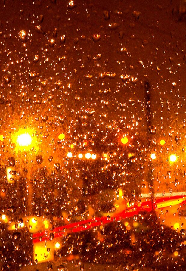 Rain on window at night with traffic outside.