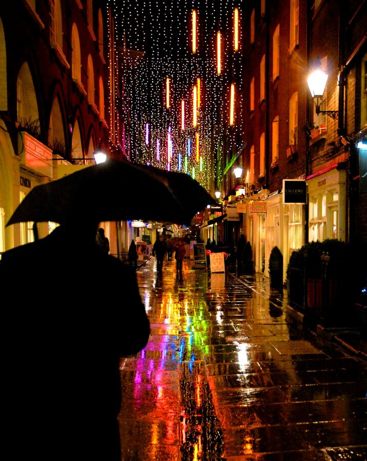 Man holding umbrella in wet street with coloured lights reflections at night