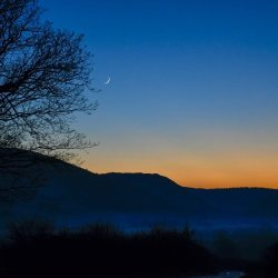 Sunset with  new Moon over a misty hilside.
