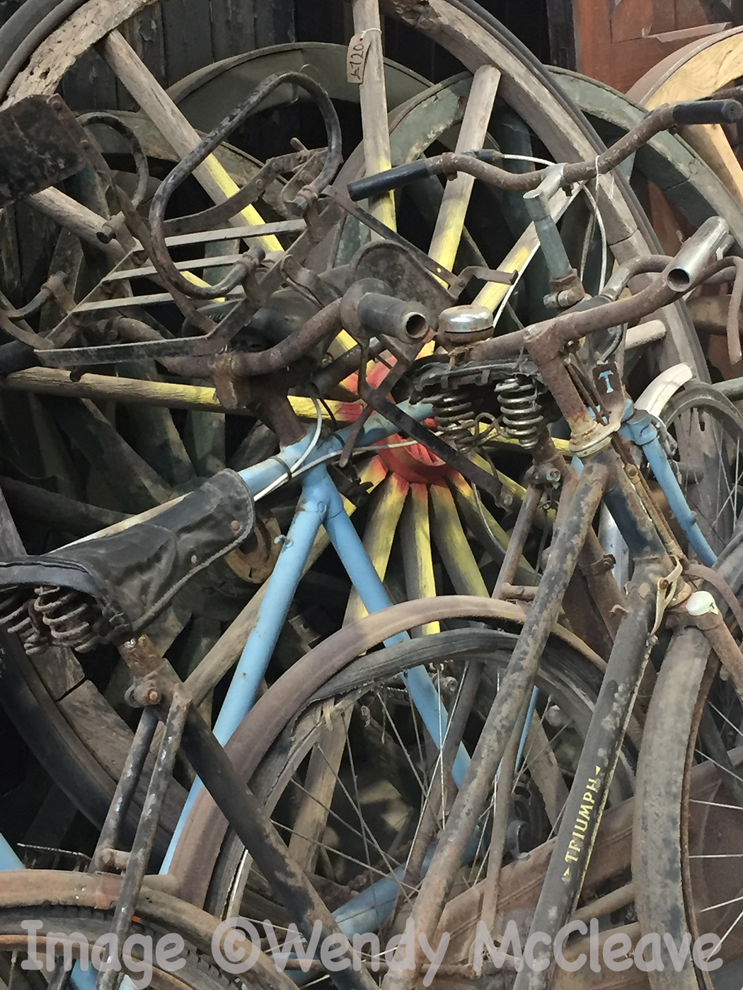 A stack of old bicycles leaning against a wall at a reclamation centre