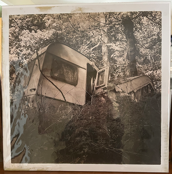 Black and white photographic print of a crushed caravan