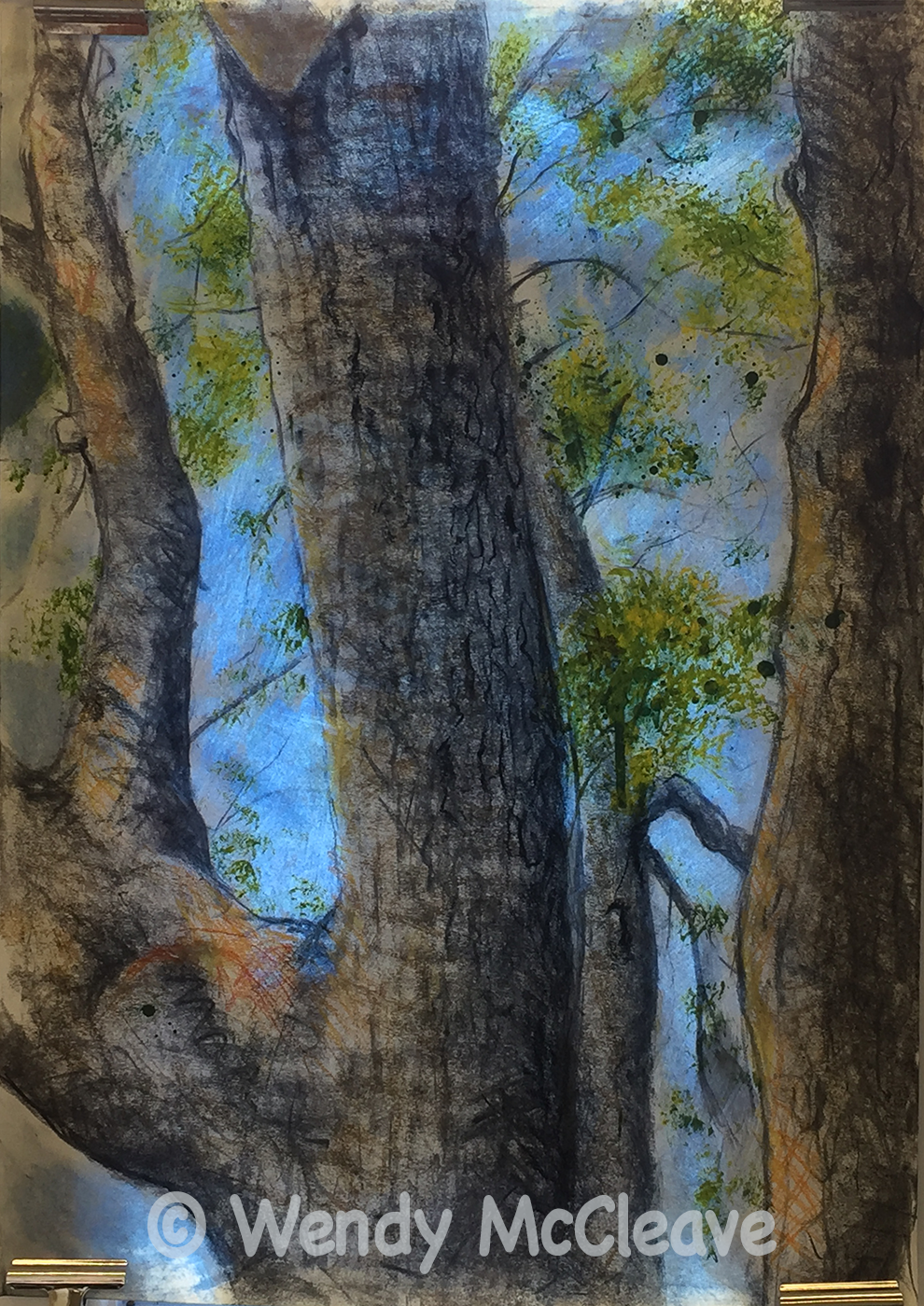 Mixed media work of trees with spring leaves against a blue sky