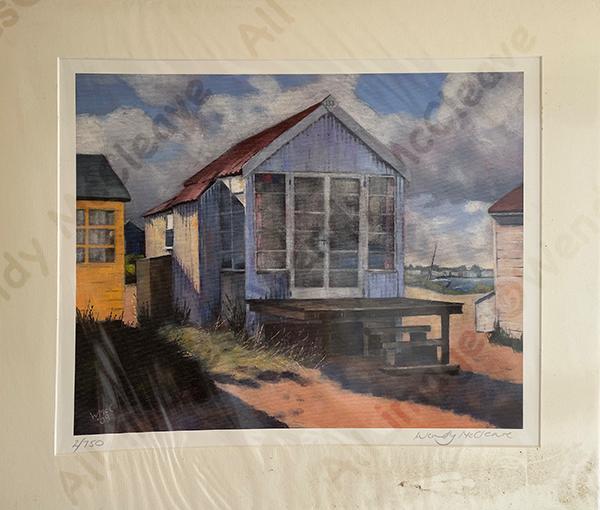 Mounted print of a tin beach hut on Mudeford Sandbank Spit under a cloudy sky