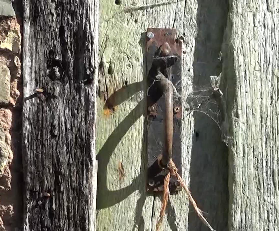 a rusty door latch on an old barn door with strong shadows