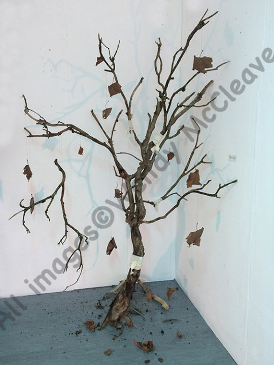 A dead tree, bandaged where cracked, with broken branch and leaves attached by invisible thread