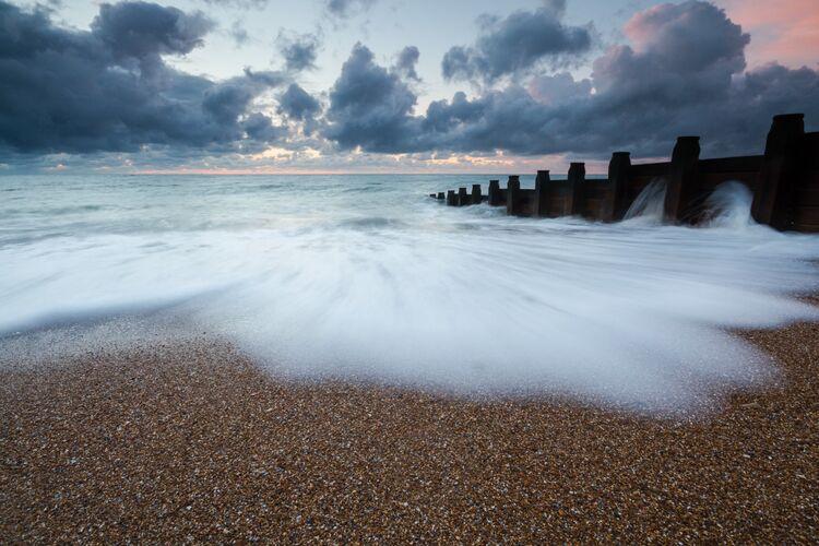 Waves crashing up the beach during sunrise
