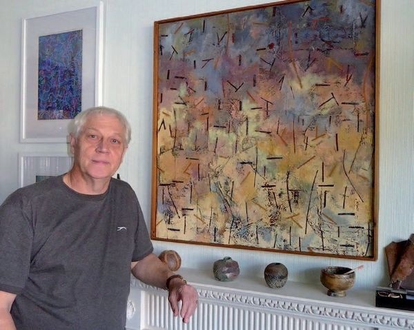 David poses with one of his paintings from the 1980s called Forest Fire